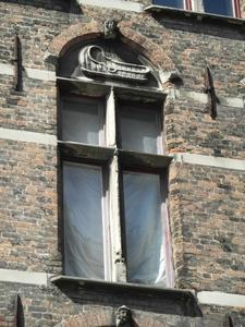 raam met kruiskozijn en boogveldversiering
