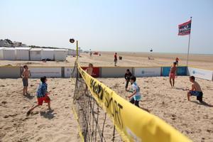 jongeren aan het volleyballen op het strand